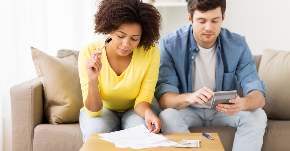 A Man and woman are sitting on a tan lounge. The woman has darker skin and is looking at pieces of paper laid out on a wooden table with a pen in her right hand. The male who has a fair complexion is looking at his calculator which is in his hands