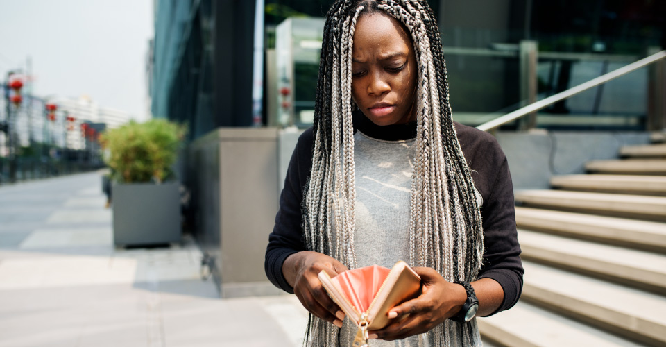 African American woman looking at her pink wallet which she has opened and it looks empty. Behind her is a building and stairs with a railing. She is outside on a footpath