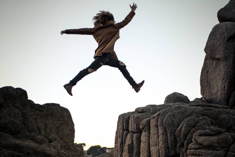 A women takes a risk and jumps between two large boulders