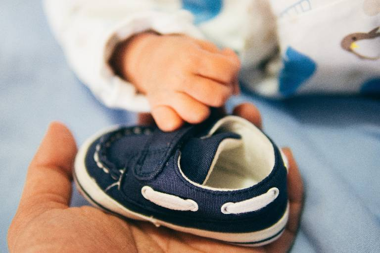 Close up of babies hand touching a baby shoe