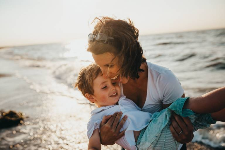 Mum holds her small child in an embrace at the beach