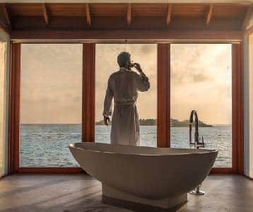 A man in a robe stands behind a large bath in front of a large window overlooking a beautiful ocean view