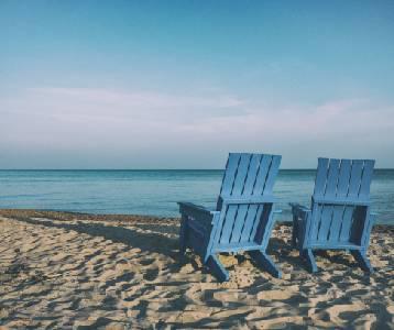 Two beach chairs on a white-sand beach facing the ocean