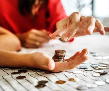 Woman counts coins while stacking them in her hand