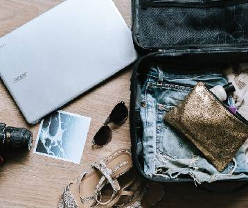 Flatlay composition of an open suitcase, a laptop, sunglasses, a camera and a photograph