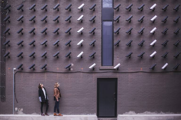 Two women looking up to a wall covered in many security cameras all pointed at them