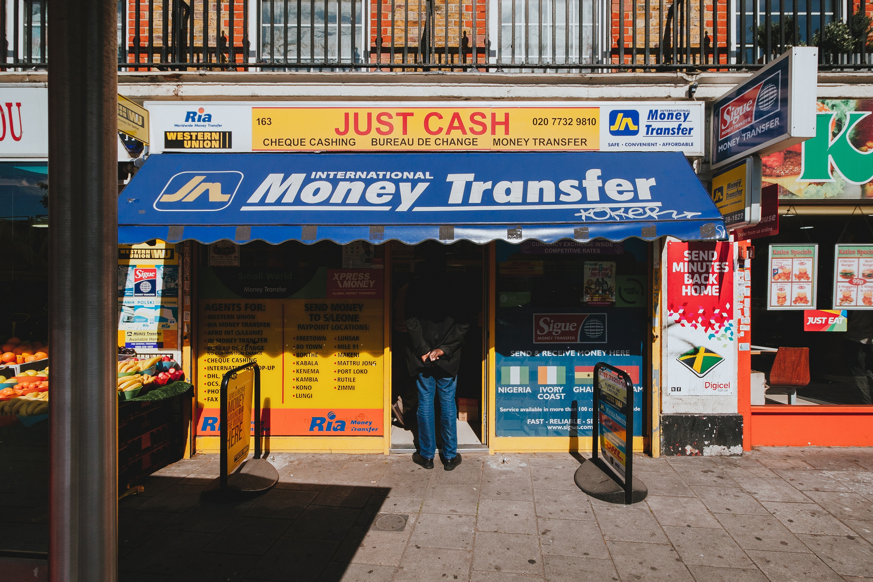A man stands with his hands behind his bank at an International Money Transfer shop