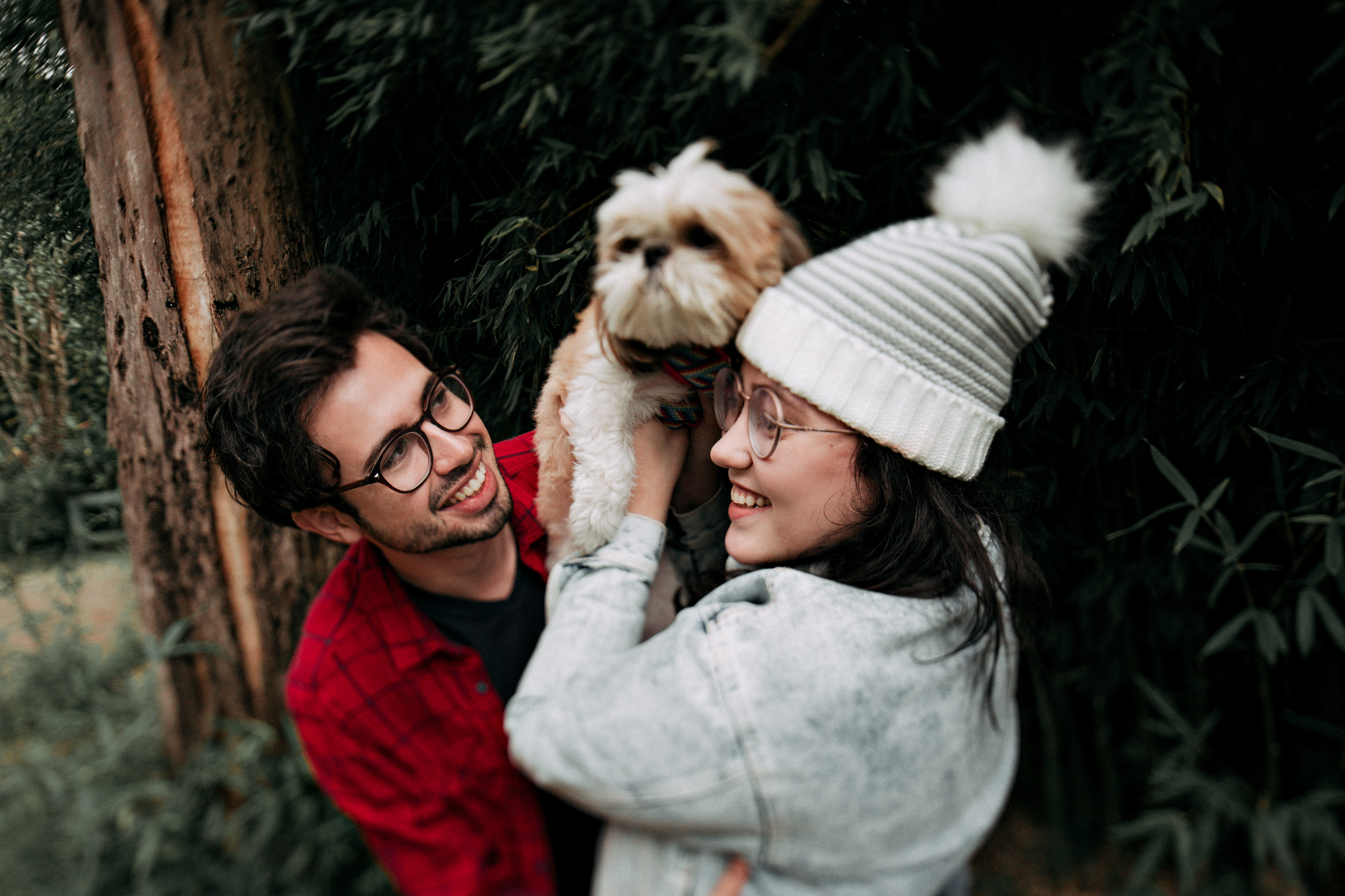 A man and a woman in winter clothes smile while they hold a fluffy white dog